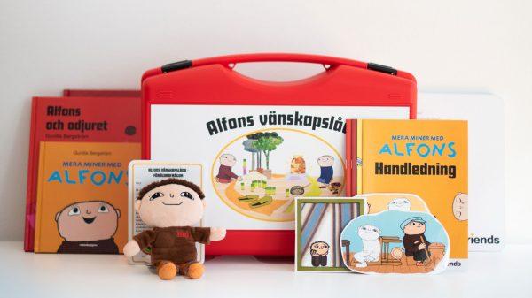 innehållet i en alfonslåda som består av böcker, en alfonsdocka samt arbetsmaterial för förskolan