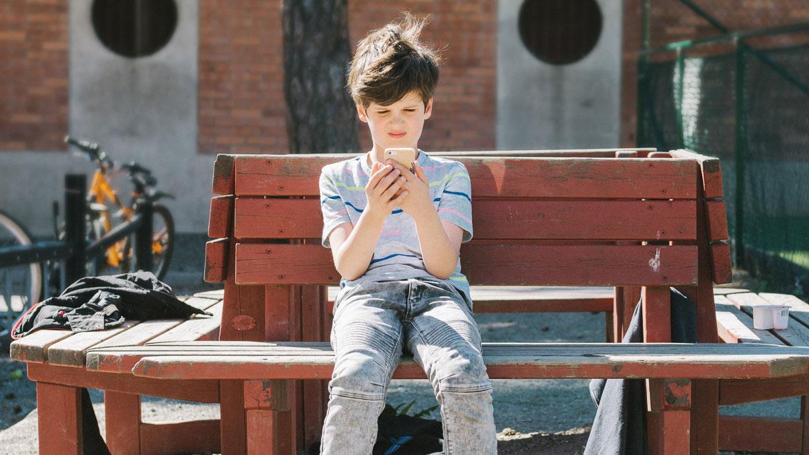 pojke sitter på en bänk med sin mobiltelefon