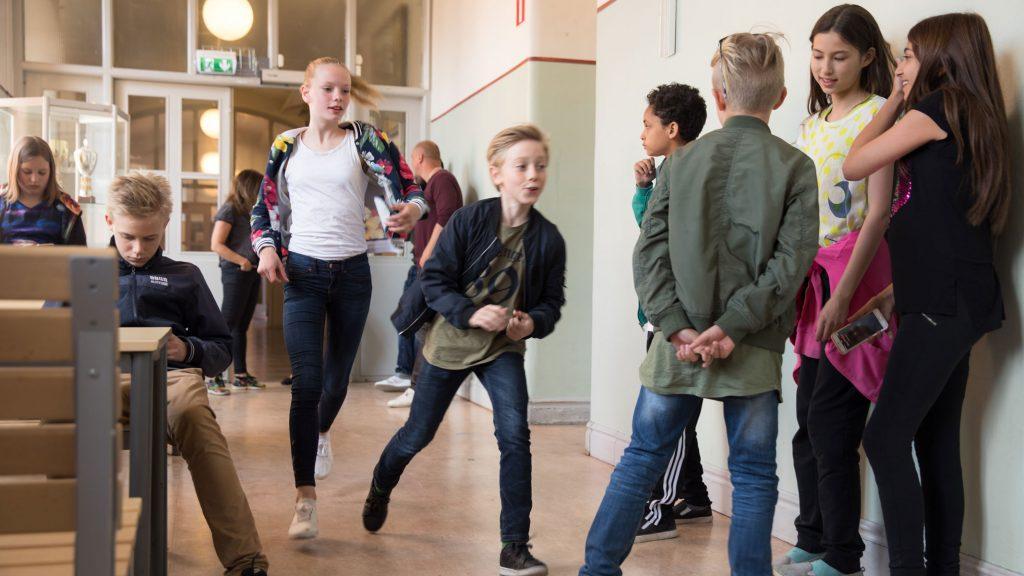 flera barn står i en skolkorridor